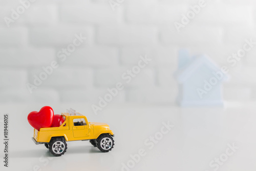 Valentines Day theme,Couple red hearts in toy yellow truck car carrying to home.Concept of love in family.