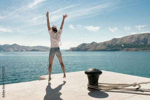 Carefree woman jumping at beach. Beautiful travel destination. Baska harbour, Krk island, Croatia.
