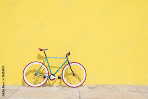 Leinwanddruck Bild A City bicycle fixed gear on yellow wall
