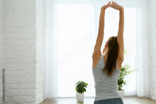 Woman Stretching Hands Near Window In Morning