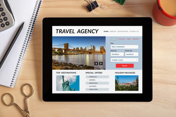 Travel agency concept on tablet screen with office objects on wooden desk. All screen content is designed by me. Top view