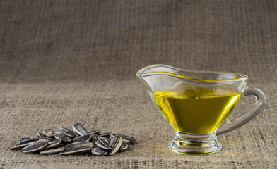 Sunflower seed oil in a glass gravy boat and a handful of sunflower seeds on the background of burlap.