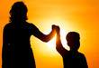 Silhouette of Mom and son in the rays of sunset