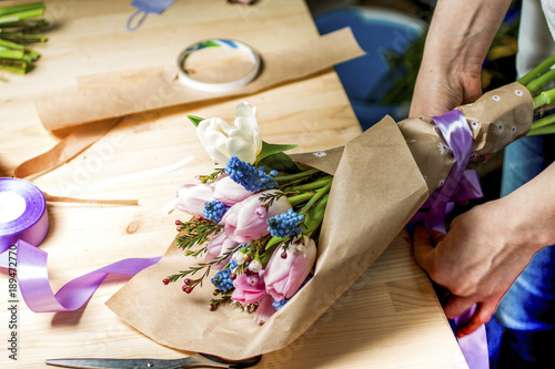 Florist at work the Assembly of a bouquet of tulips in a wrapper made of paper