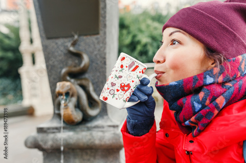 Happy woman drinks water from a hot thermal spring in Karlovy Vary, Czech Republic at winter time