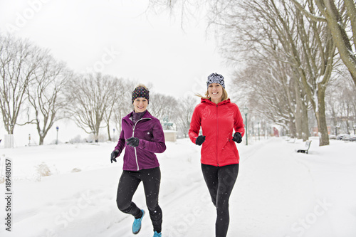 Group of friends enjoying jogging in the snow in winter