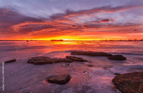 Foto op Plexiglas Ochtendgloren Colorful Sunrise or Sunset on a frozen lake with rocks in the foreground