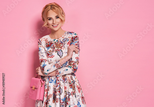 Leinwanddruck Bild Fashion photo of a beautiful elegant young woman in a pretty dress with flowers holding handbag posing over pink background. Fashion photo