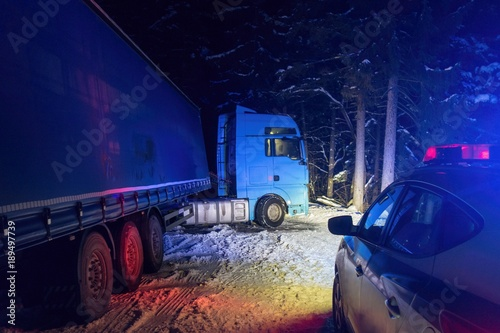 fototapeta na ścianę A real accident. Truck traffic accident at night, on a snowy winter road. Broken truck on the road in the snow.
