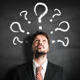 Geschäftsmann mit vielen Fragezeichen auf Schiefertafel