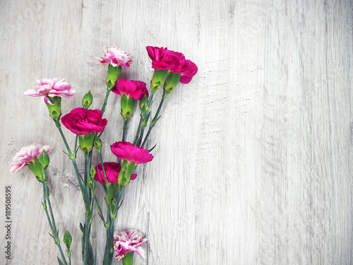 Flowers of carnations on a wooden light background