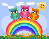 Three bright, cartoonish, beautiful, pink owls with bows on the ear sit on the rainbow