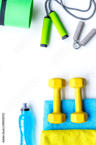 Do fintess in gym. Dumbbells, jump rope, expander, mat, water on white background top view copy space