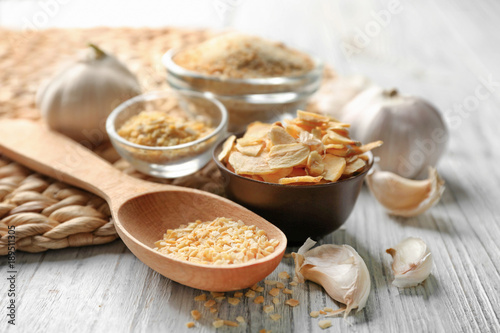 Fotobehang Kruiden 2 Spoon with granulated dried garlic on wooden background