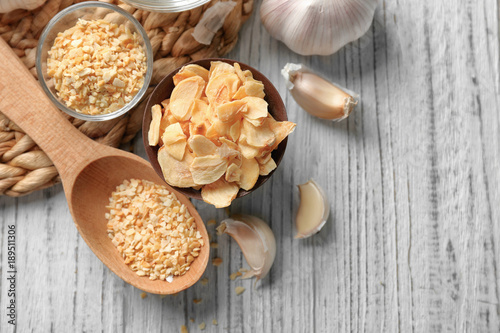 Fotobehang Kruiden 2 Composition with granulated dried garlic and flakes on wooden background