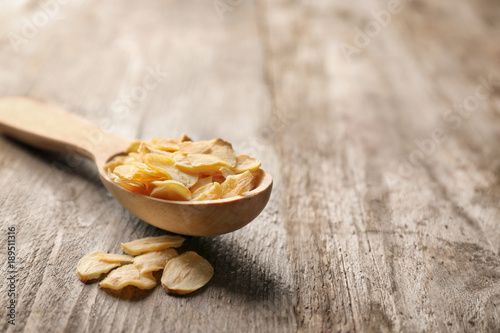 Fotobehang Kruiden 2 Spoon with dried garlic flakes on wooden background