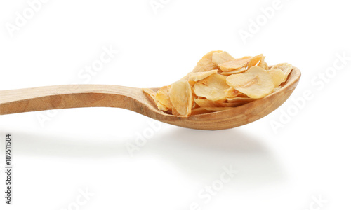 Fotobehang Kruiden Dried garlic flakes in spoon on white background