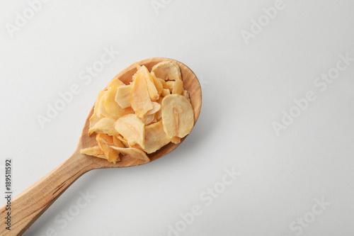 Fotobehang Kruiden 2 Dried garlic flakes in spoon on white background