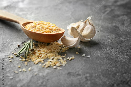 Fotobehang Kruiden 2 Wooden spoon with granulated dried garlic on grey background