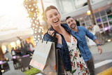 Cheerful girl pulling on boyfriend's arm to go shopping - 189513551