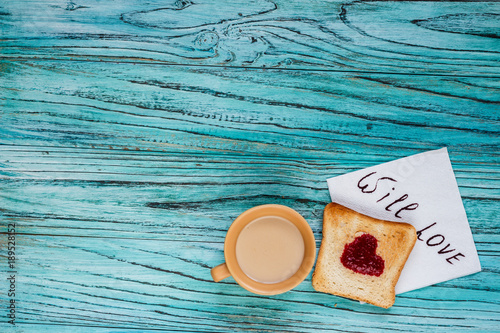 On a wooden background there is a cup of coffee with a toast on which a jam in the form of a heart. Valentine's day concept.