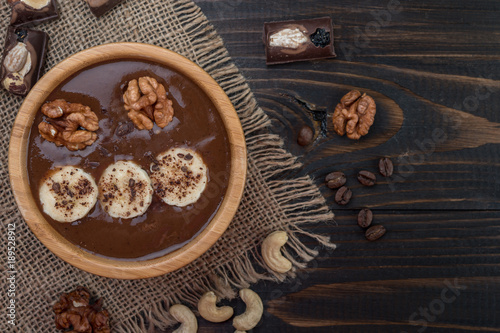 Foto op Aluminium Milkshake Fresh chocolate smoothie on a bowl on wooden background, top view