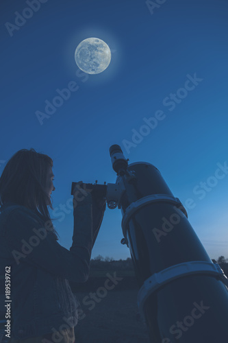 Girl looking at the Moon through a telescope.  - 189539762