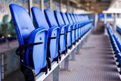 Empty blue plastic chairs in a row at the football stadium.