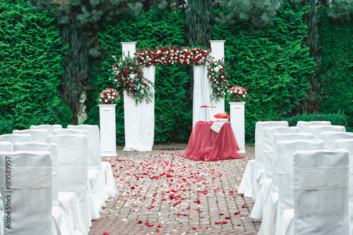 Wedding ceremony. Arch, decorated with red and white roses, in the ...