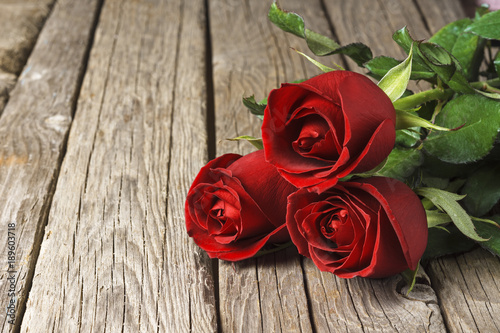 Red roses on old wooden table, Valentine's Day background
