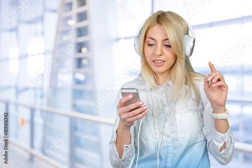 Fotobehang Muziek Happy young blonde woman listening to music