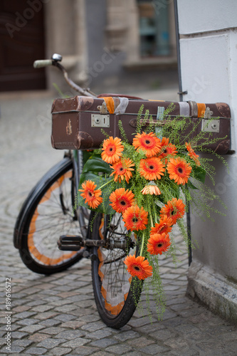 Foto op Canvas Fiets flowered retro bicycle decorated with orange flowers, gerberas