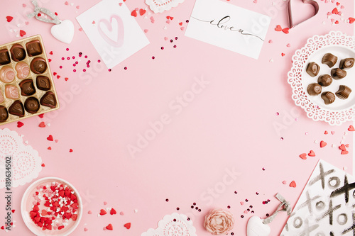 Valentine's Day, love concept. Mock up frame made of confetti, heart symbol accessories, sweets, postcards on pink background. Flat lay, top view.