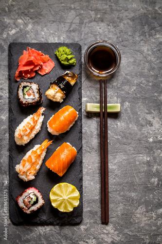 Aluminium Sushi bar sushi and sushi rolls, sushi nigiri on stone plate on dark background, mustard wasabi, and ginger