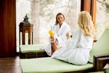 Cheerful women in bathrobes drinking juice in spa center
