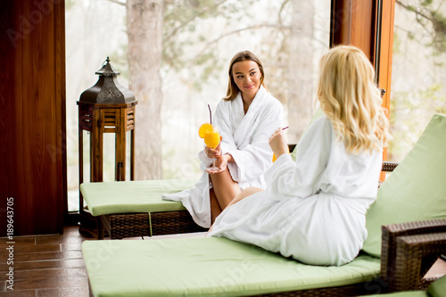 Fotobehang Spa Cheerful women in bathrobes drinking juice in spa center
