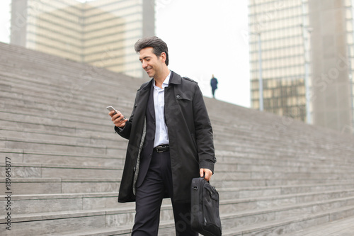 business man walking using smartphone to watch photos.