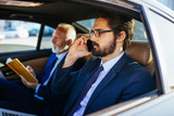 Fototapety Senior businessman and his assistant sitting in limousine and working