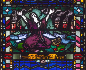 LONDON, GREAT BRITAIN - SEPTEMBER 16, 2017: The scene of The sorrow in the captivity of the Jews in Babylon on the stained glass in church St Etheldreda by Charles Blakeman (1953 - 1953).