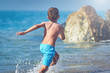 Cute Caucasian boy is running in the water along the sea shore against big boulders.