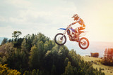 Fototapety Racer on motorcycle participates in motocross cross-country in flight, jumps and takes off on springboard against sky. Concept active extreme rest.