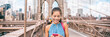 Happy woman using phone walking in NYC on Brooklyn Bridge. New York city lifestyle young Asian girl commuting or summer travel tourist on USA vacation. Banner panorama.