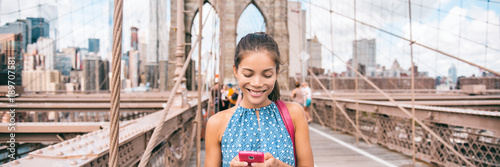 Foto Murales Happy woman using phone walking in NYC on Brooklyn Bridge. New York city lifestyle young Asian girl commuting or summer travel tourist on USA vacation. Banner panorama.