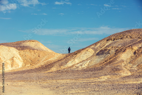 Foto op Aluminium Blauw Desert landscape. Man standing on mountain in desert