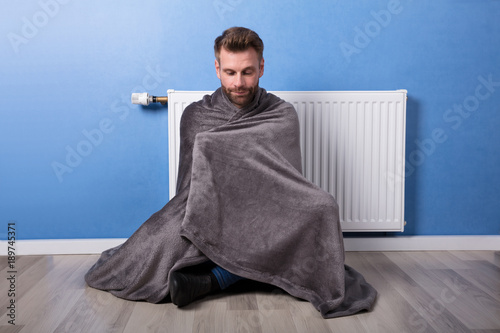 Foto Murales Man Sitting In Front Of Heater At Home