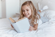 Quadro smiling kid lying on bed and reading book