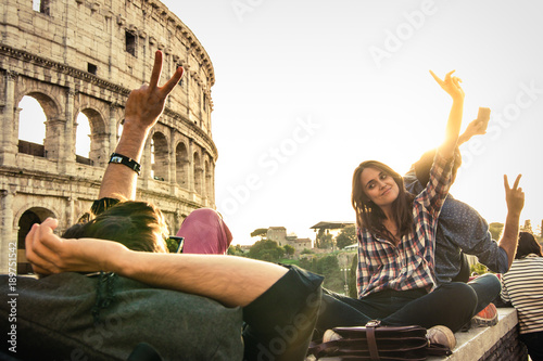 Three young friends tourists sitting lying in front of colosseum in rome taking selfie pictures with smartphone camera. Sunset with lens flare.