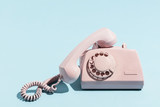 Oldschool pink telephone on a blue background - 189752972