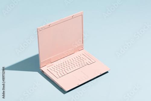 Retro pink laptop on a pastel blue background.
