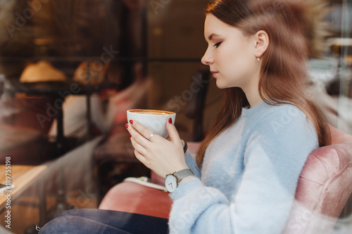 Portrait of girl hold coffee cup and look at camera. Stylish clothing wear. Autumn and winter weather. Blur background. Proffesional photo. © shipskyy